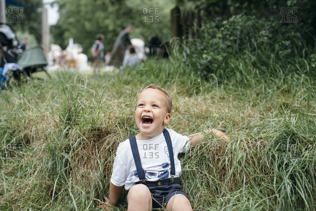 Toddler boy laughing in bed of tall grass