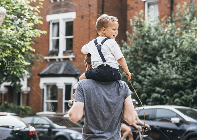 Happy toddler turning around on father's shoulders outside