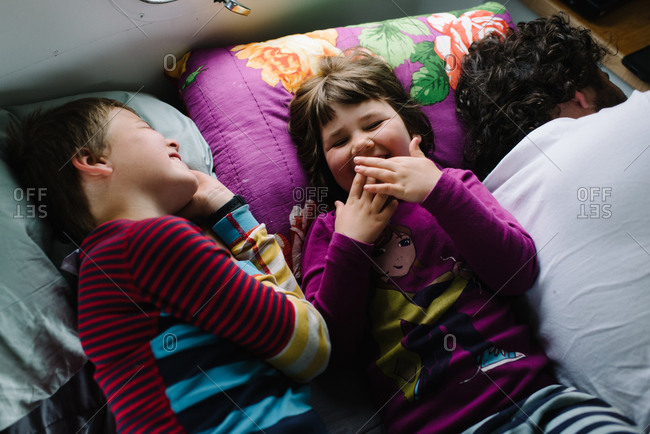 Two kids lying beside father in camper laughing