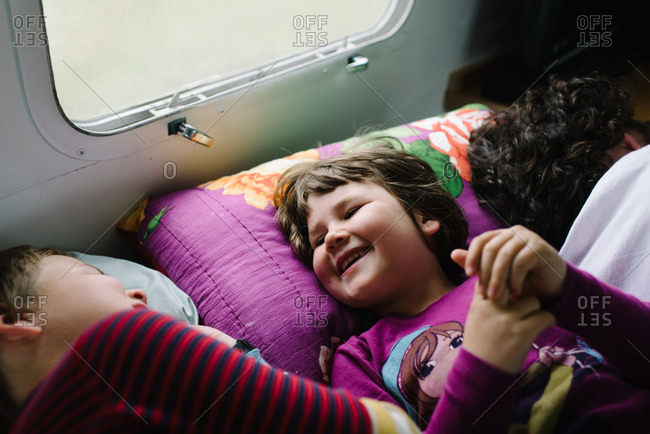 Kids lying beside father in camper laughing