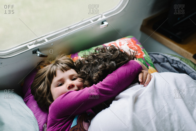 Girl hugging father in camper bed