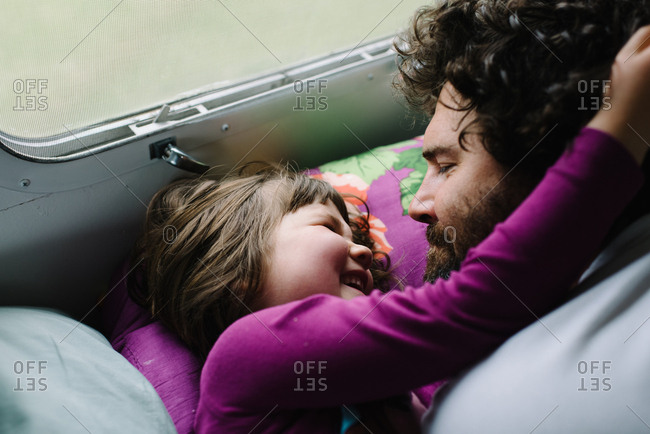 Girl waking father up with a hug in camper bed