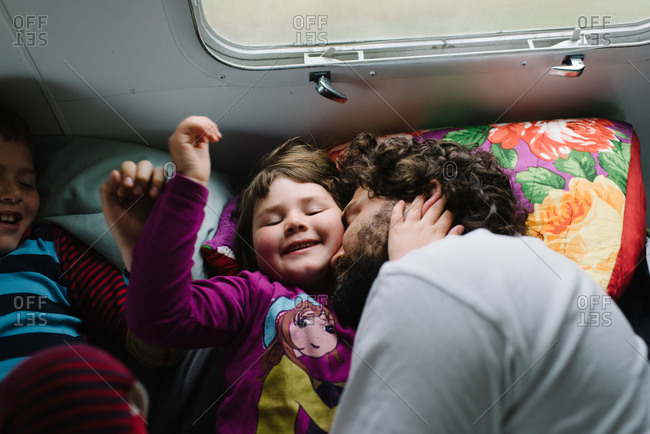 Kids lying beside father in camper bed