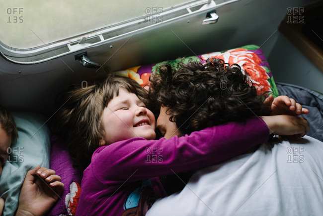 Girl hugging dad in camper bed