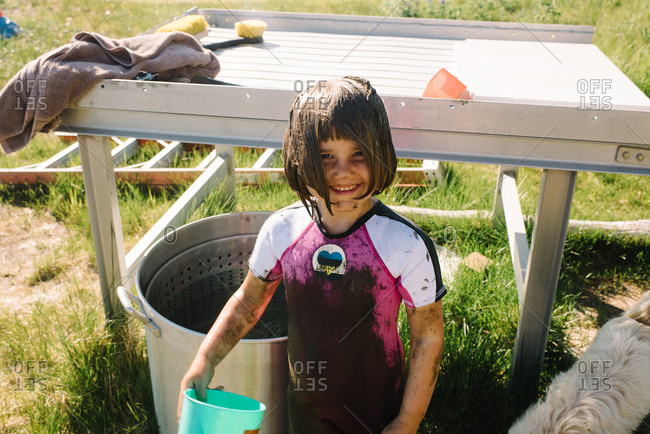 Little girl wearing muddy wetsuit