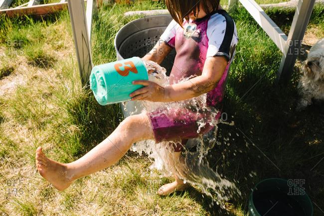 Little girl wearing muddy wetsuit splashing herself with water