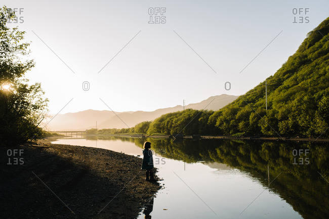 Silhouette of young girl on a riverbank in Alaska at sunset