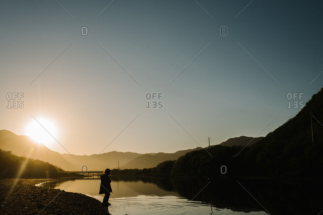 Young girl stepping into a river in Alaska at sunset