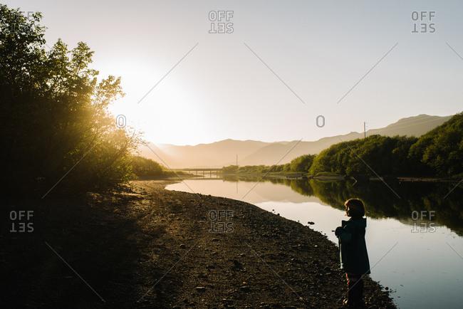 Young girl splashing in a riverbank in Alaska at sunset