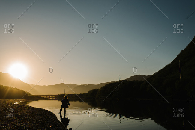 Young girl walking in a river in Alaska at sunset