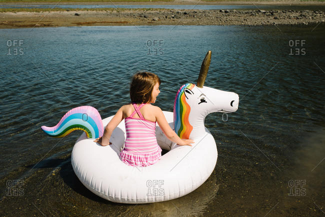 Little girl floating on a unicorn raft