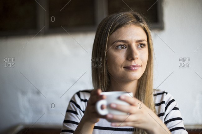 Woman drinking a cup of coffee looking away in a cafe in Madrid, Spain