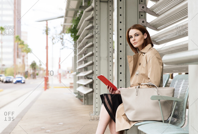 Business woman waiting at tram stop