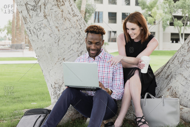 Male and female work colleagues working outdoors under a tree on their laptop
