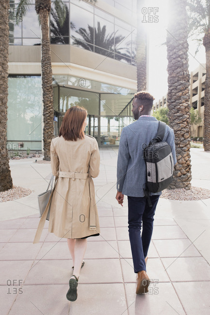 Male and female work colleagues walking to office