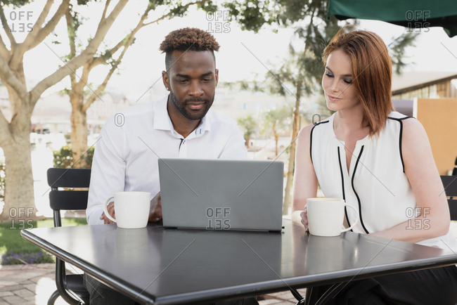 Male and female colleagues having coffee and working on laptop outside