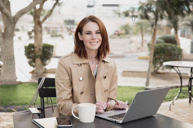 Businesswoman working outside on laptop