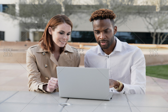 Male and female work colleagues working on a laptop outdoors