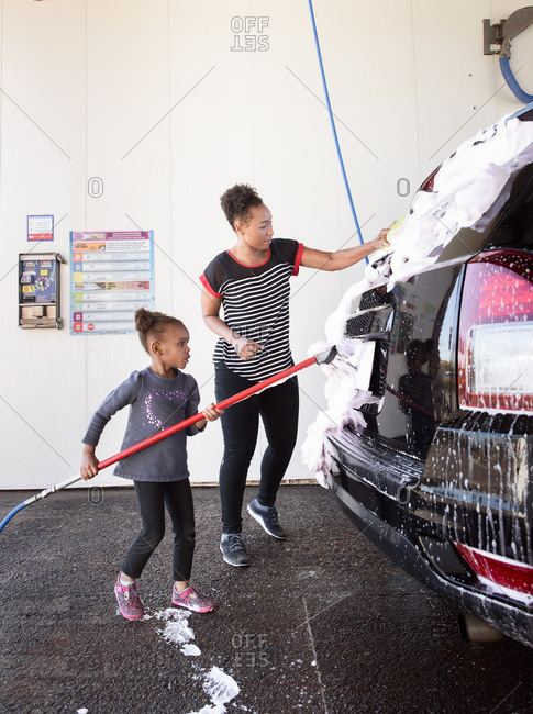 Mother and daughter washing the car at the carwash