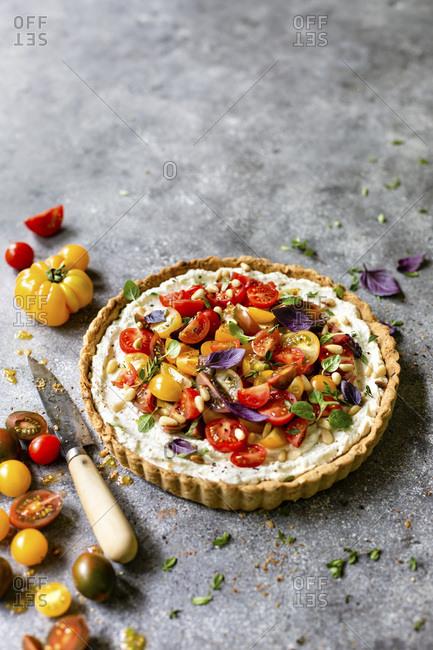 Heirloom tomato ricotta tart on a gray background