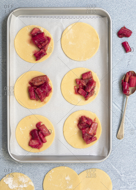 Short crust pastry circles on a baking tray filled with spoonfuls of roasted rhubarb