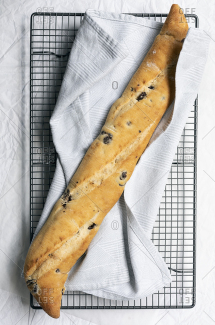 A crusty olive baguette cooling on a wire rack