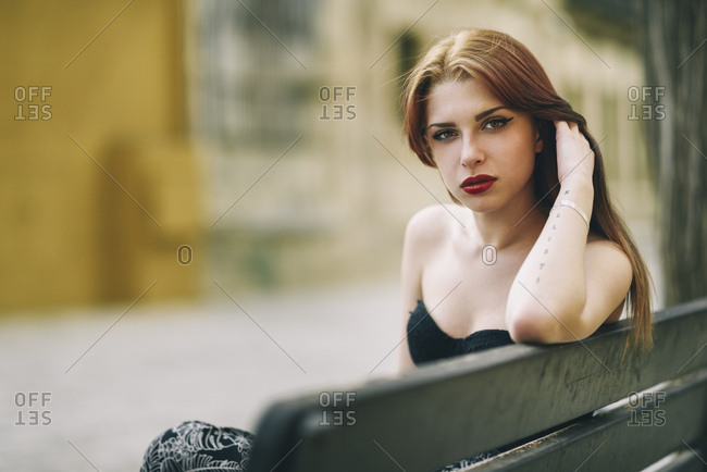 Young woman sits on a urban bench