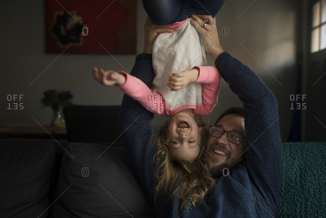 Father holding his laughing daughter upside down