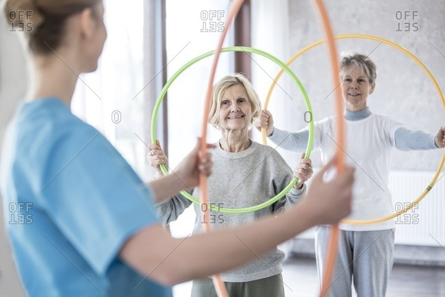 Physiotherapist with two senior women holding plastic hoops