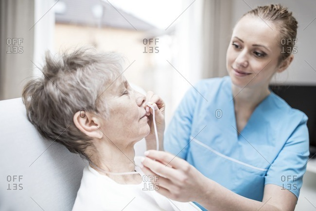Care worker inserting nasal cannula in senior woman