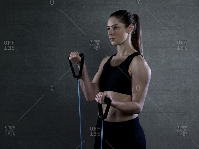 Young woman in sports top with resistance band, portrait