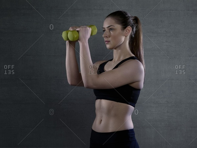 Young woman in sports top holding hand weights, portrait