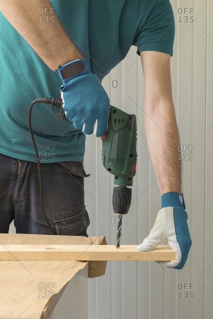 Carpenter using electric drill