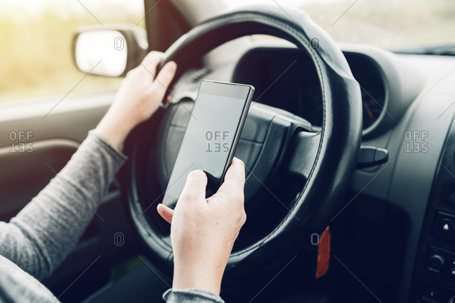 Woman driving and using smartphone