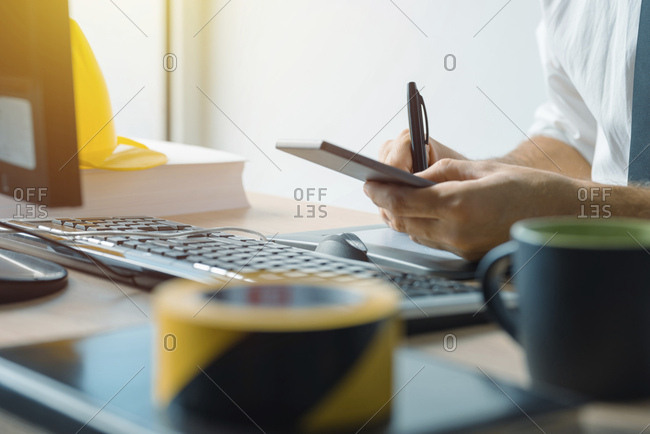 Civil engineer using smartphone in office