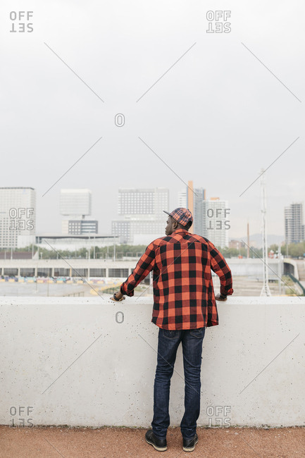Handsome black men looking towards the city, wearing casual clothing. Back view.