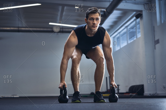 Man doing kettlebell exercise at gym