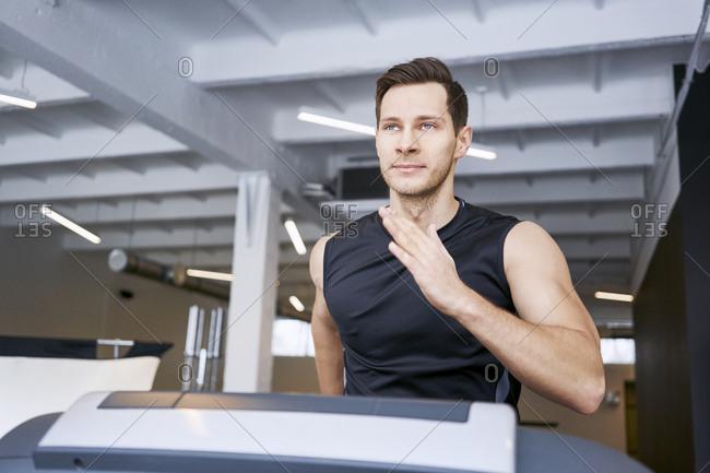 Portrait of man running on treadmill at gym