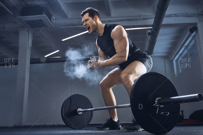 Motivated weightlifter clapping hands before barbell workout at gym