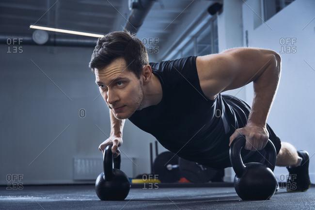 Man doing pushups on kettlebells at gym