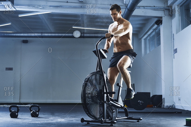 Athletic man doing HIIT workout on air bike at gym