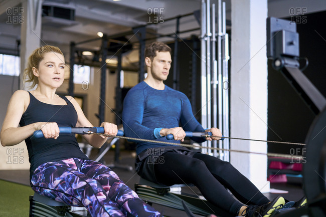 Man and woman at gym exercising together on rowing machines