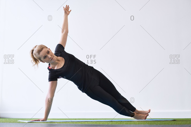 Woman doing side plank yoga exercise in studio