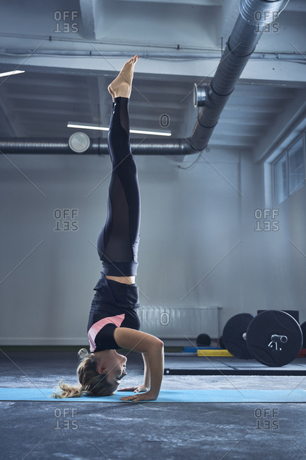 Woman doing headstand yoga exercise at gym