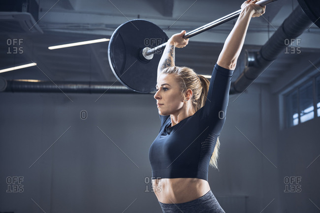 Woman doing push press exercise at gym