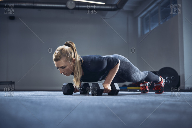 Woman practicing dumbbell push-up exercise at gym