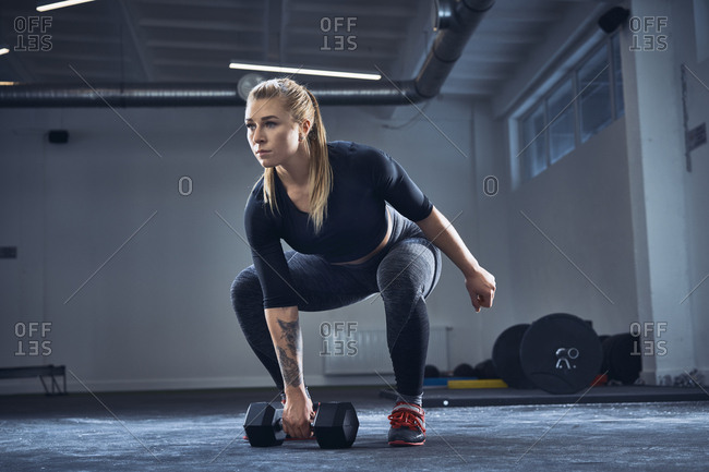 Woman doing dumbbell exercise at gym