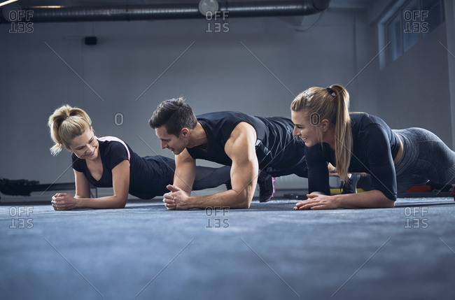 Three people doing plank exercise at gym