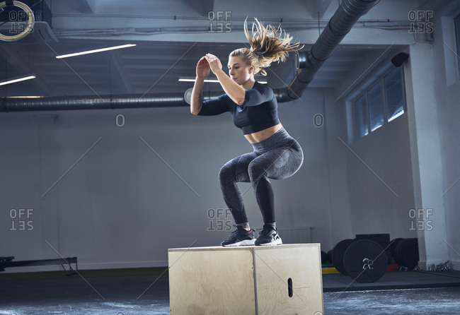 Athletic woman doing box jump exercise at gym