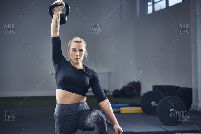Woman doing kettlebell exercise at gym
